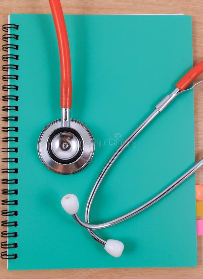 Stetoscopio rosso che si trova su un Libro verde sottile fotografia stock libera da diritti