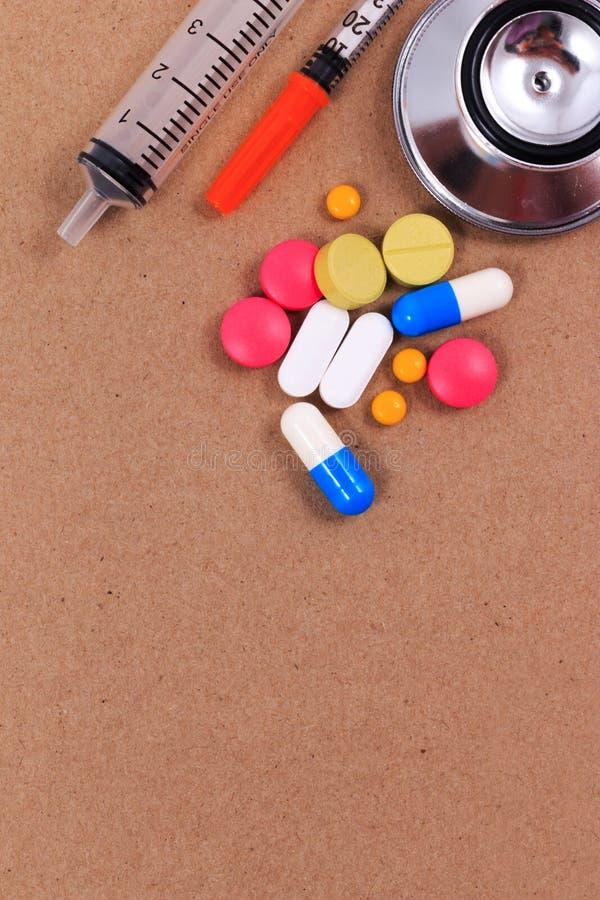 Stetoscopio rosso, siringhe e molte pillole variopinte immagine stock libera da diritti