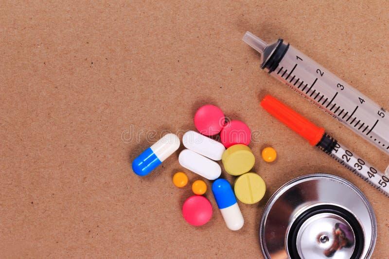 Stetoscopio rosso, siringhe e molte pillole variopinte fotografia stock libera da diritti