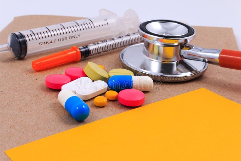 Stetoscopio rosso, siringhe, nota appiccicosa e molte pillole variopinte fotografie stock libere da diritti