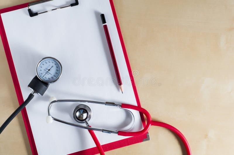 Stetoscopio rosso, tonometer e matita rossa su una lavagna per appunti rossa Vista superiore Giusto spazio della copia Apparecchi fotografie stock