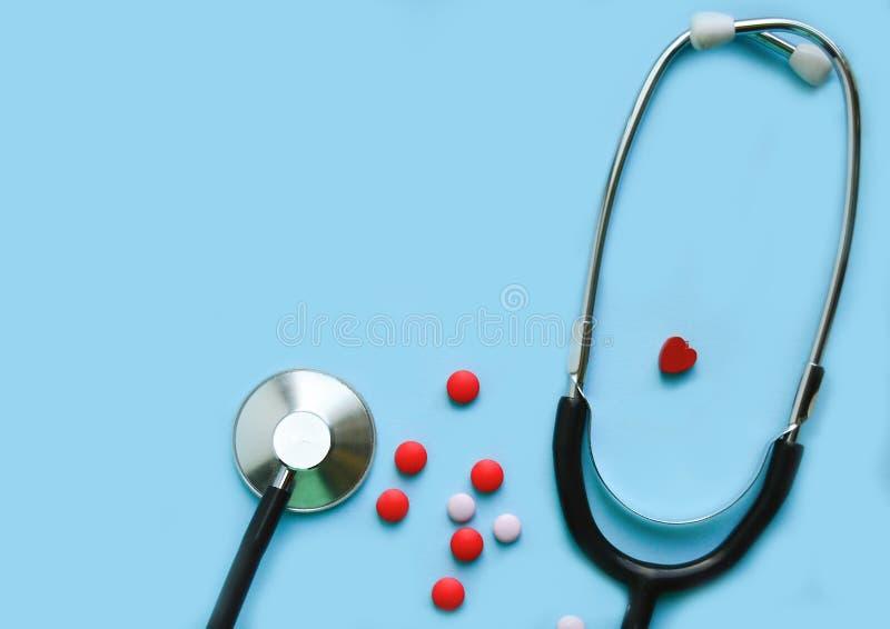 Stetoscopio su un fondo blu con le pillole e un cuore rosso, spazio libero fotografia stock libera da diritti
