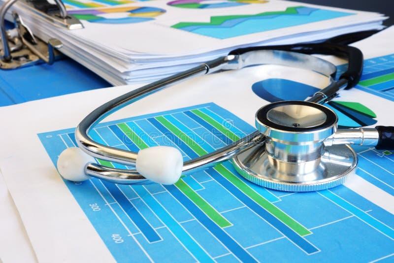 Stetoscopio su un rapporto finanziario Analisi commerciale e verifica immagine stock