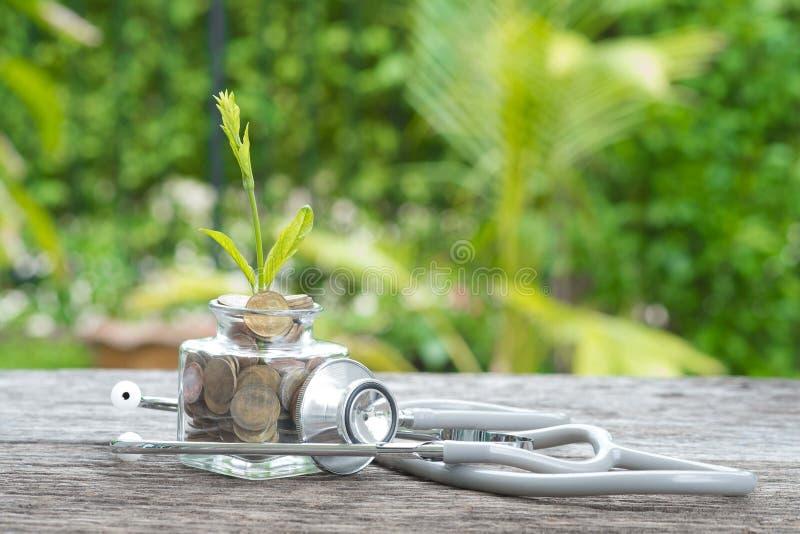 Stetoscopio sulla bottiglia, sulla moneta e sulla pianta su fondo di legno Concentrato fotografia stock
