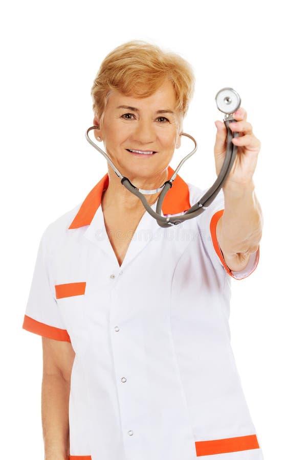 Stetoskop för äldre kvinnlig doktor för leende hållande fotografering för bildbyråer