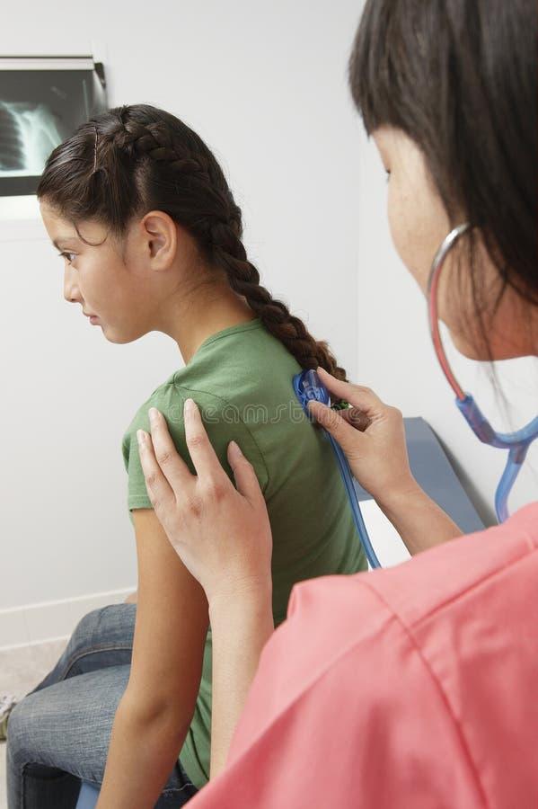Stetoskop för doktor Examining Girl Using arkivfoton