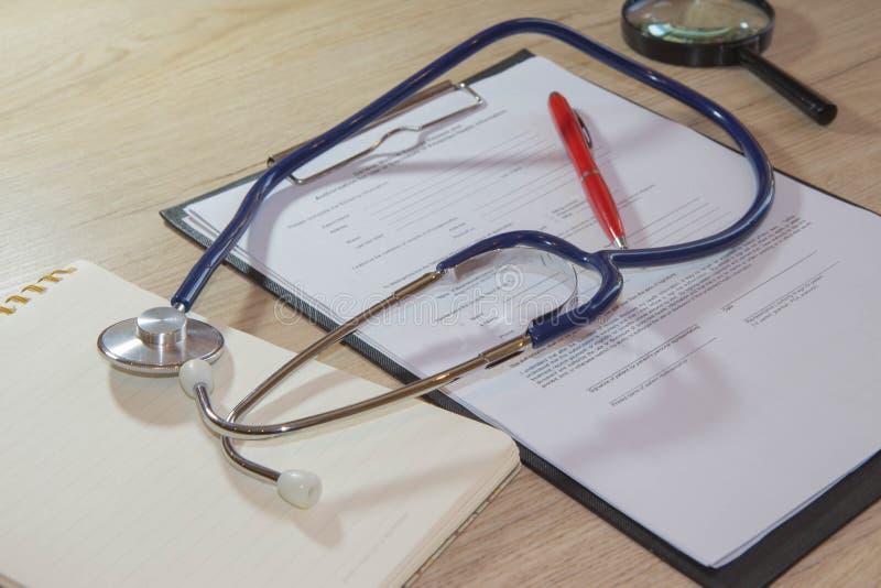 Stetoskop i pióro na książeczce zdrowia Pojęcie wizerunek zdrowie czeki zdjęcia royalty free