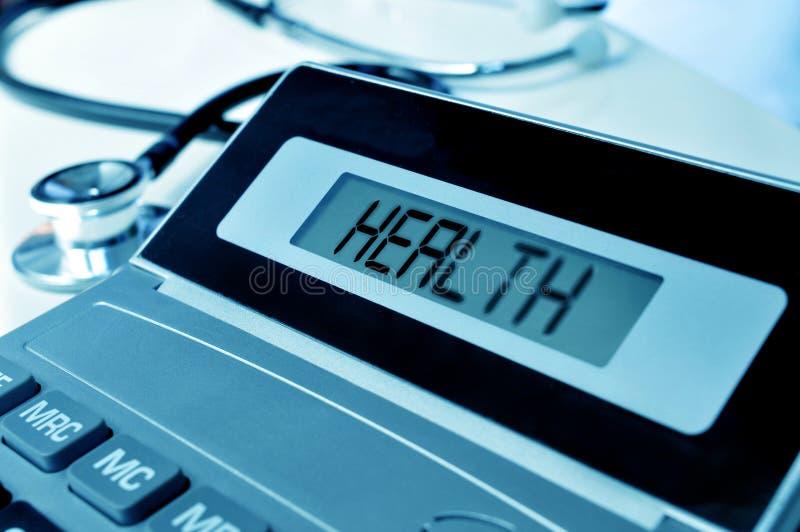 Stetoskop i słów zdrowie w pokazie kalkulator fotografia royalty free
