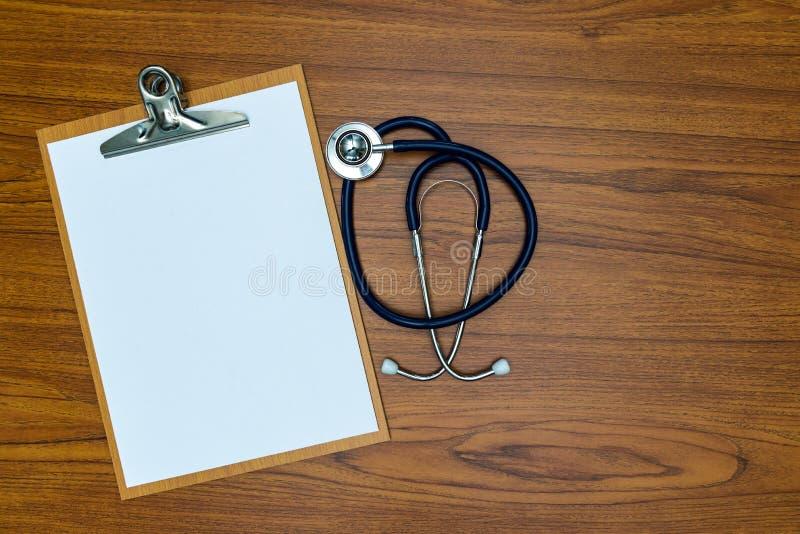 Stetoskop i schowek z pustym białym papierem ciąć na arkusze na drewnie t obraz stock