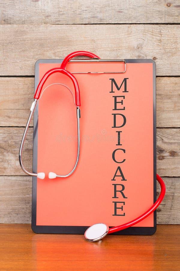 stetoskop i schowek z tekstem & x22; MEDICARE& x22; na drewnianym biurka tle zdjęcia stock