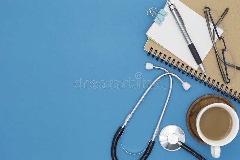 Stetoskop med anteckningsboken, blyertspenna, vitbok, kaffekopp, exponeringsglas arkivbild