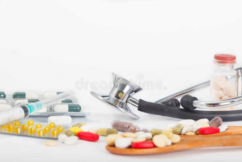 Stetoskop med olika mediciner, preventivpillerar, ampules och injektionssprutor arkivbilder