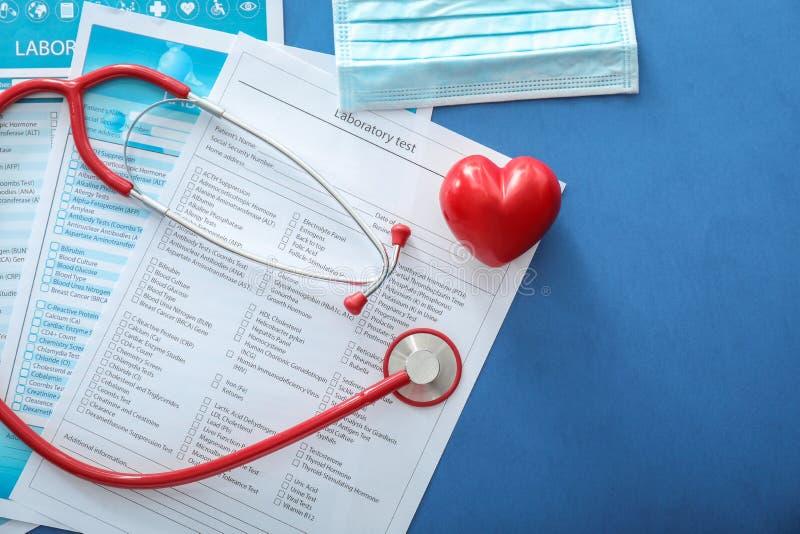 Stetoskop med röd hjärta och listor av laboratoriumprov på färgbakgrund band f?r m?tt f?r ?pplebegreppsh?lsa royaltyfria bilder