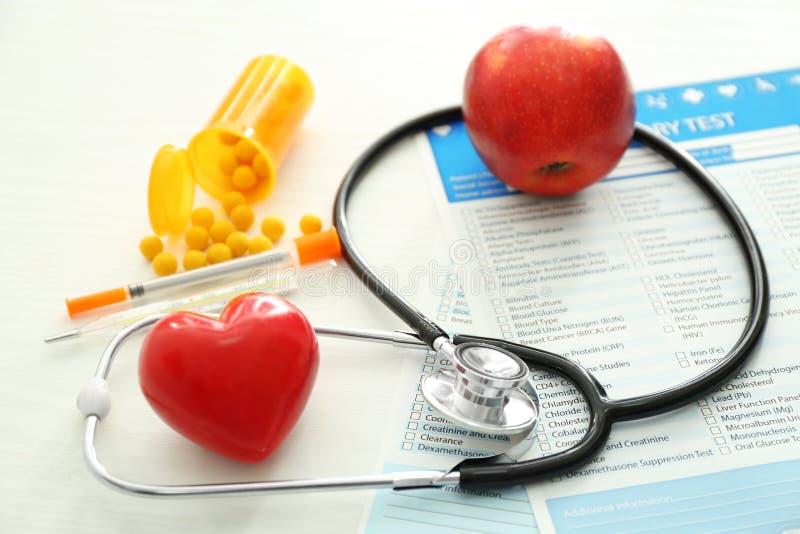 Stetoskop med röd hjärta och listor av laboratoriumprov på vit bakgrund bakgrund suddighetdde den skyddande pillen f?r maskeringe royaltyfri fotografi