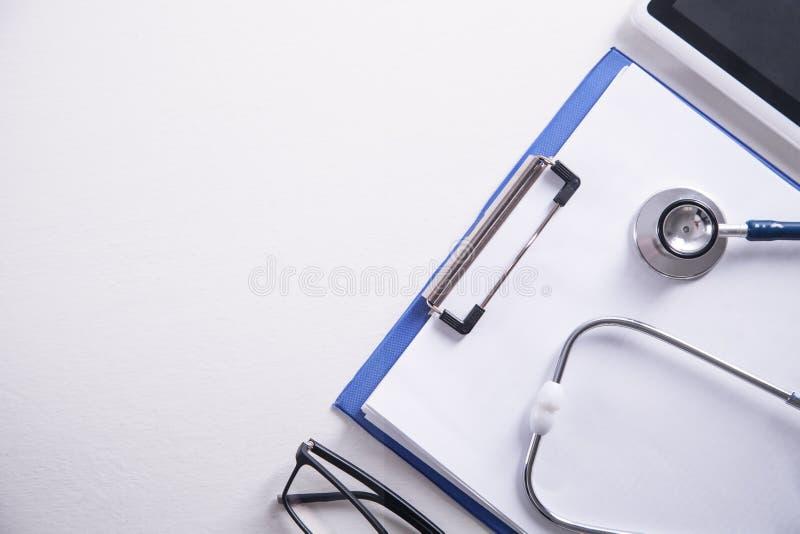 Stetoskop, medicinskrivplatta, minnestavla och exponeringsglas Doktorsarbetsplats arkivbild