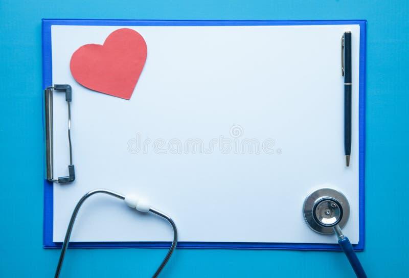 Stetoskop, medicinskrivplatta, penna och röd hjärta Doktorsarbetsplats arkivfoton