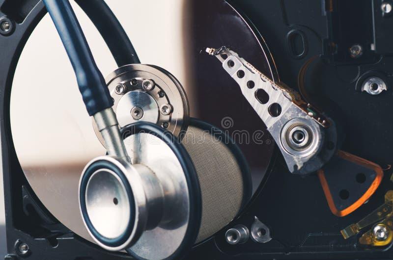 Stetoskop na starym zakurzonym demontującym dysku twardym od komputeru nad ciemnym tłem zdjęcia stock
