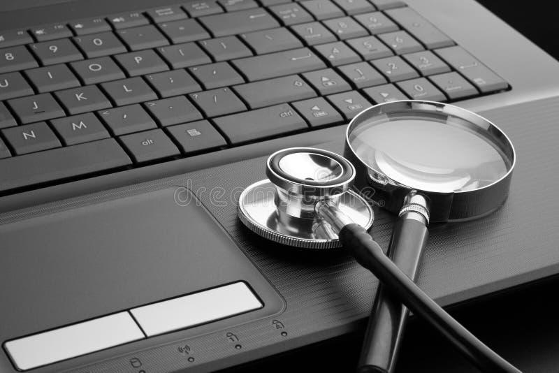 Stetoskop och förstoringsglas på bärbar dator royaltyfri foto