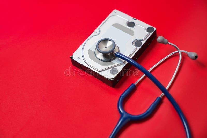 Stetoskop- och hårddiskdrev på röd bakgrund Diagnostisk datormaskinvara och reparationsbegrepp arkivbild