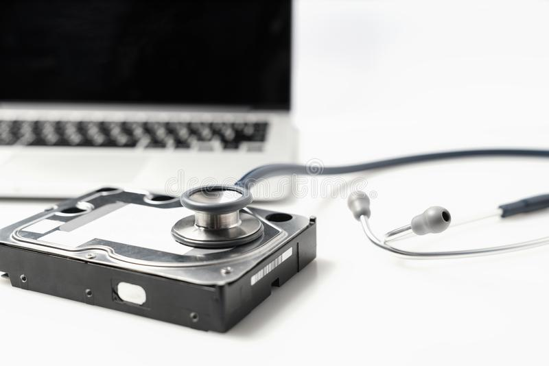 Stetoskop- och hårddiskdrev på vit bakgrund Diagnostisk datormaskinvara och reparationsbegrepp arkivfoto
