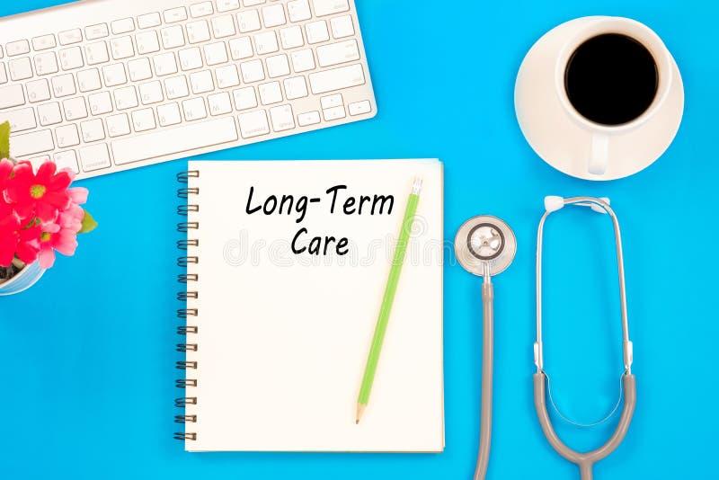 Stetoskop på anteckningsboken och blyertspennan med långsiktiga omsorgord som arkivfoton