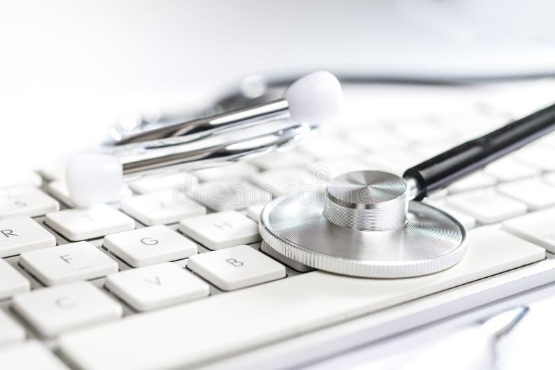 Stetoskop på den vita tabellen med datortangentbordet arkivbilder