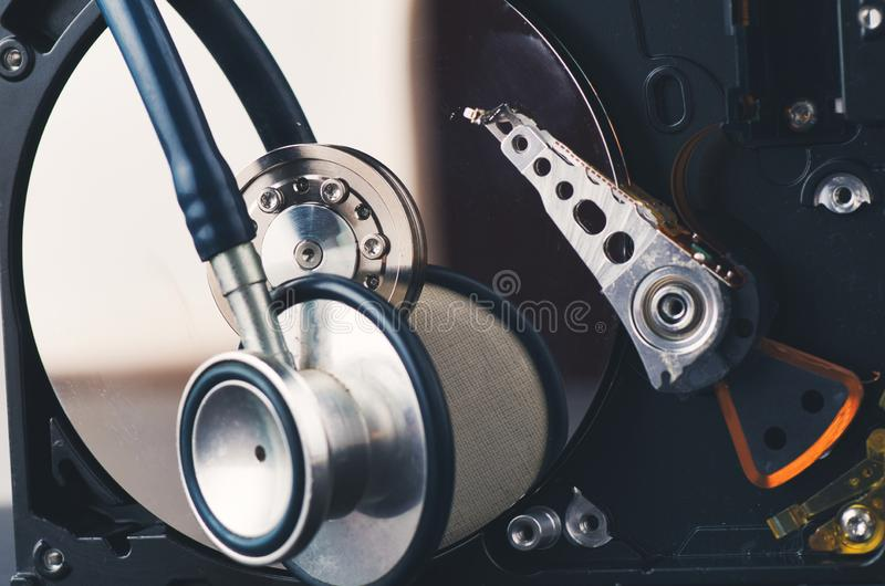 Stetoskop på gammal dammig demontera hårddisk från datoren över mörk bakgrund arkivfoton