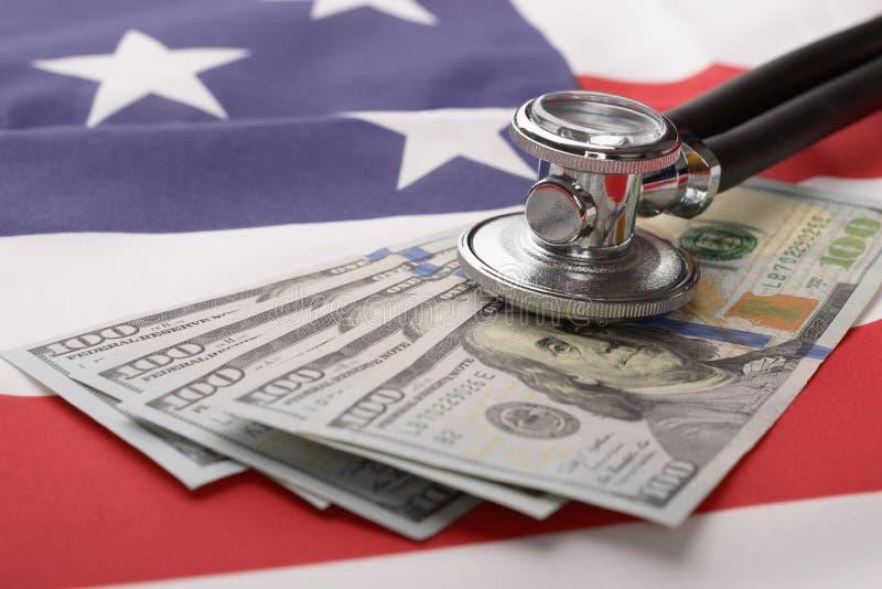 Stetoskop på oss valuta och amerikanska flaggan royaltyfri fotografi