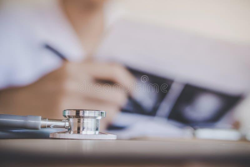 Stetoskop på skrivbordet med doktorn som i regeringsställning arbetar royaltyfria bilder