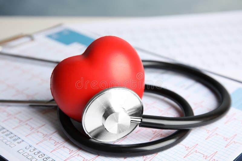Stetoskop, röd hjärta och kardiogram på tabellen royaltyfri foto
