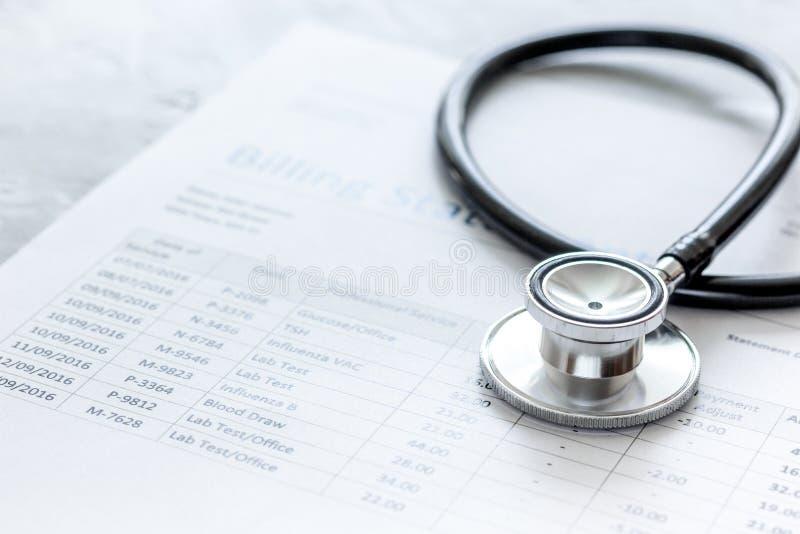 Stetoskop som fakturerar meddelandet för arbete för doktors` s i vårdcentralstenbakgrund royaltyfri foto