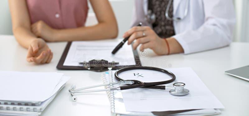 Stetoskopet den medicinska receptformen ligger mot bakgrunden av en doktor och en patient som diskuterar vård- examen arkivbilder