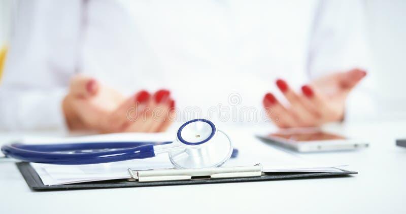 Stetoskopet den medicinska receptformen ligger mot bakgrunden av en doktor och en patient som diskuterar vård- examen royaltyfri fotografi