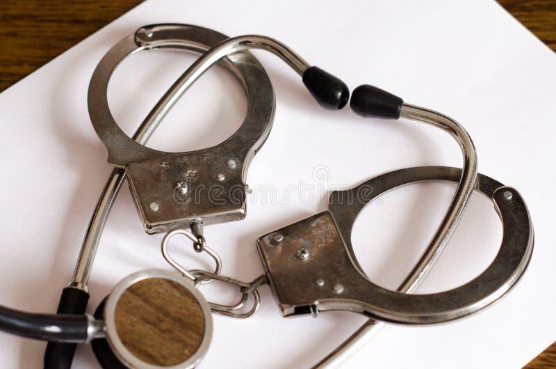 Stetoskopu i kajdanek pojęcie pomyłka lekarska fotografia stock