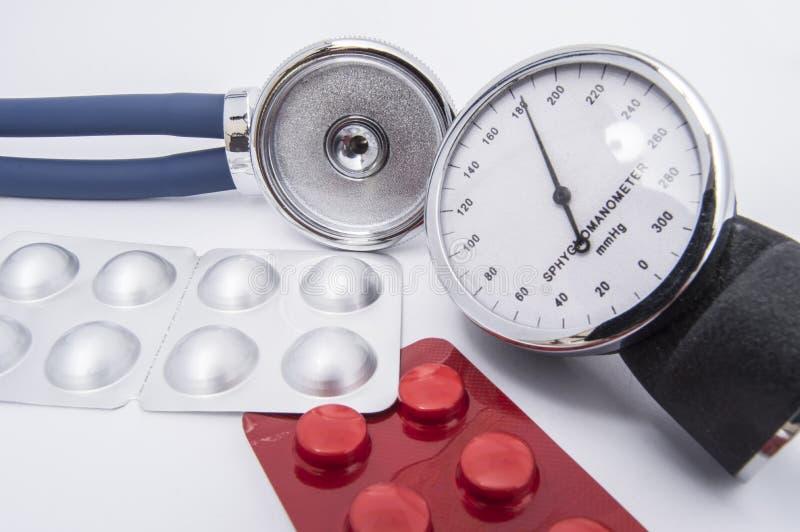 Stetoskopu i sphygmomanometer tarcza z wysokimi wskaźnikami arterialny ciśnienie krwi kłama na białym medycznym stole blisko  zdjęcie stock