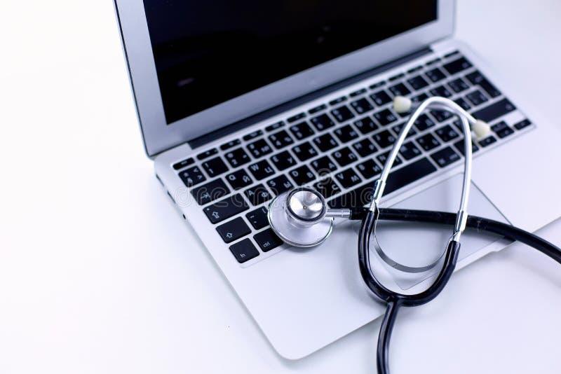 Stetoskopu lying on the beach na laptop klawiaturze w pojęciu online medycyna lub troubleshooting komputer przeglądał niskiego ką zdjęcia stock
