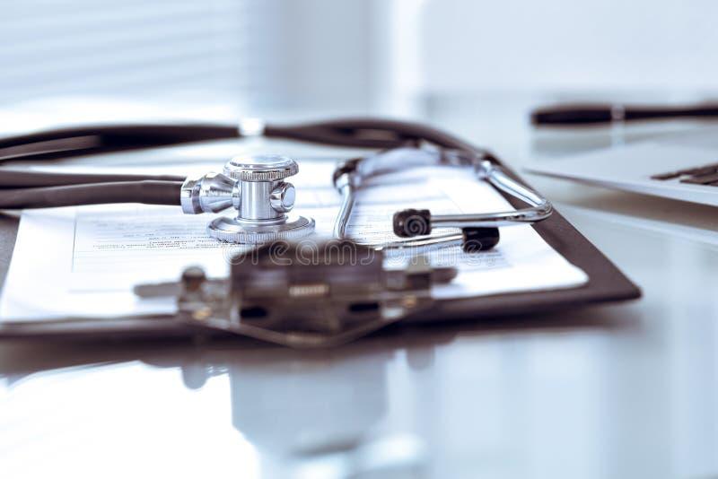 Stetoskopu lying on the beach przy biurkiem z medycznej historii laptopem i rejestrami Medycyny ` s pracuj?cego sto?u doktorski p fotografia royalty free