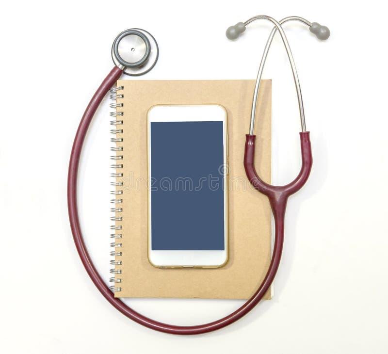Stetoskopu telefon komórkowy i brown notatnik na białym tle, mieszkanie nieatutowy zdjęcie royalty free