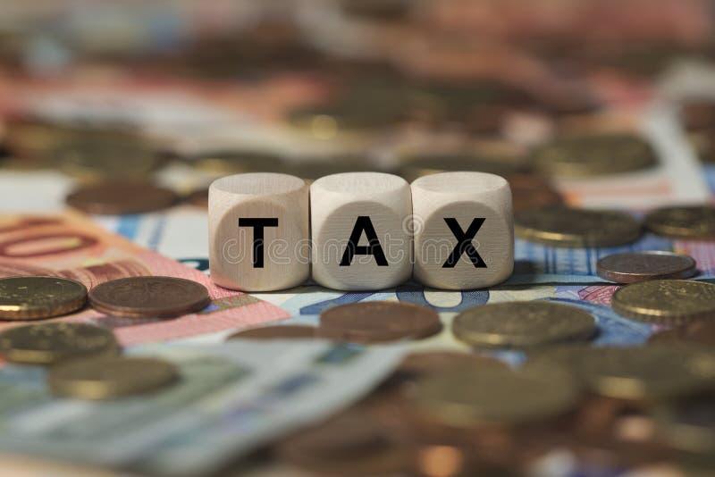 Steuer- Würfel mit Buchstaben, Geldsektorausdrücke - unterzeichnen Sie mit hölzernen Würfeln stockfotografie