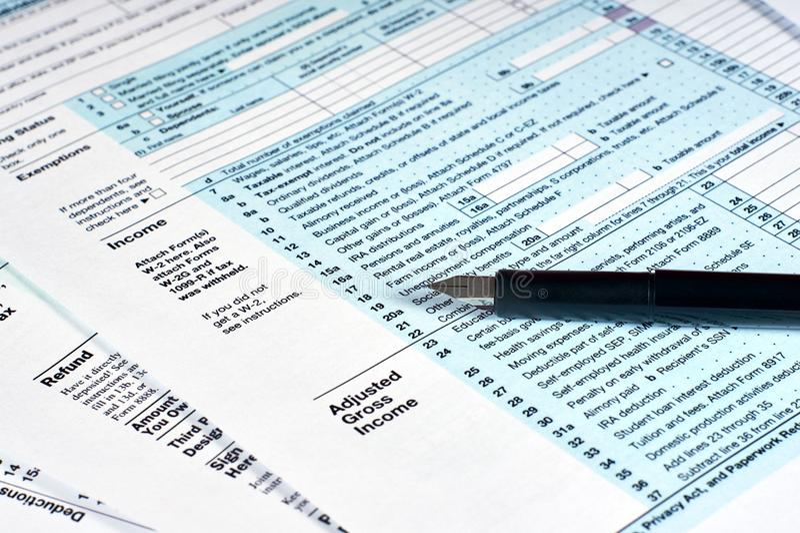 Steuerbericht Steuerformulare ergänzen lizenzfreie stockfotografie