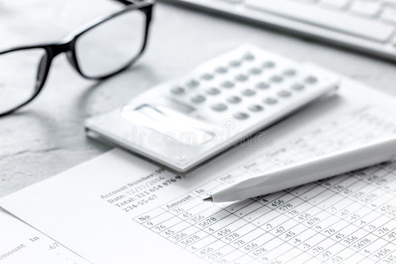Steuerbuchhaltung mit Taschenrechner im Büroarbeitsplatz auf Draufsicht des Steinschreibtischhintergrundes stockbild