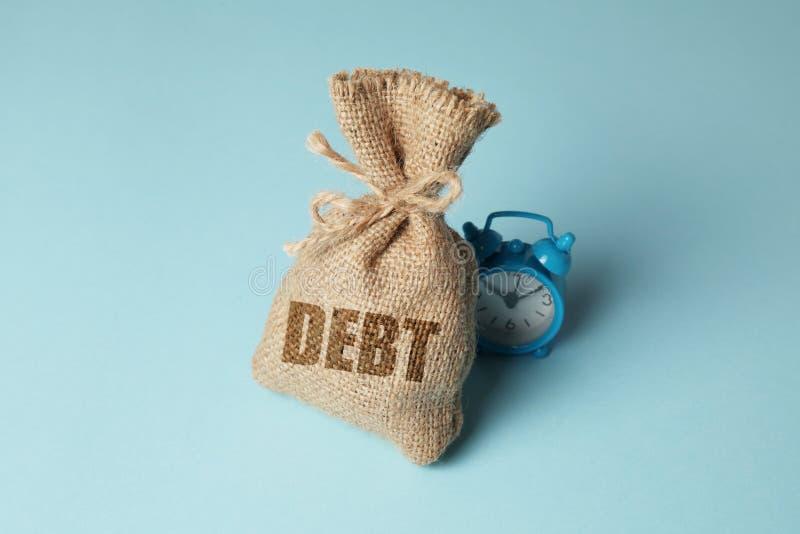 Steuern und Zinsen auf Schuldenzahlungen Überfällige Zahlungen, Strafen Tasche mit Geld und Uhr auf blauem Hintergrund stockfotografie