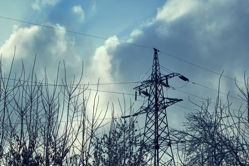 Steun of torenmachtslijnen tegen de donkere hemel en boomtakken stock afbeelding