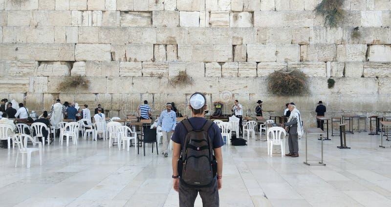 Steun van een jonge toerist in vrijetijdskleding en kippah op het hoofd bekijkend de loeiende muur en het godsdienstige bidden di royalty-vrije stock fotografie