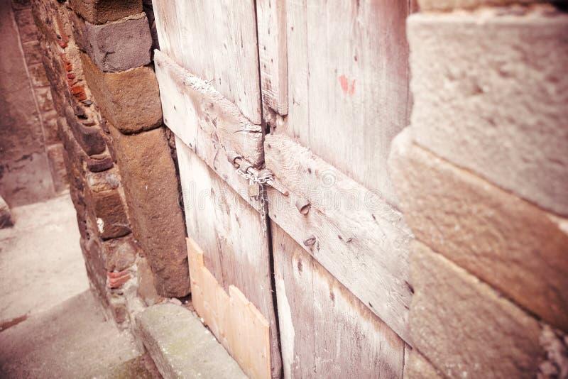 Stevige oude die deur door een omheining, de bescherming van veiligheidsconcepten wordt geblokkeerd stock afbeeldingen