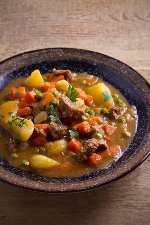 Stew, που γίνονται με το βόειο κρέας, πατάτες, καρότα και πράσινα μπιζέλια Goulash σούπα σε ένα κύπελλο στον ξύλινο πίνακα στοκ φωτογραφία με δικαίωμα ελεύθερης χρήσης