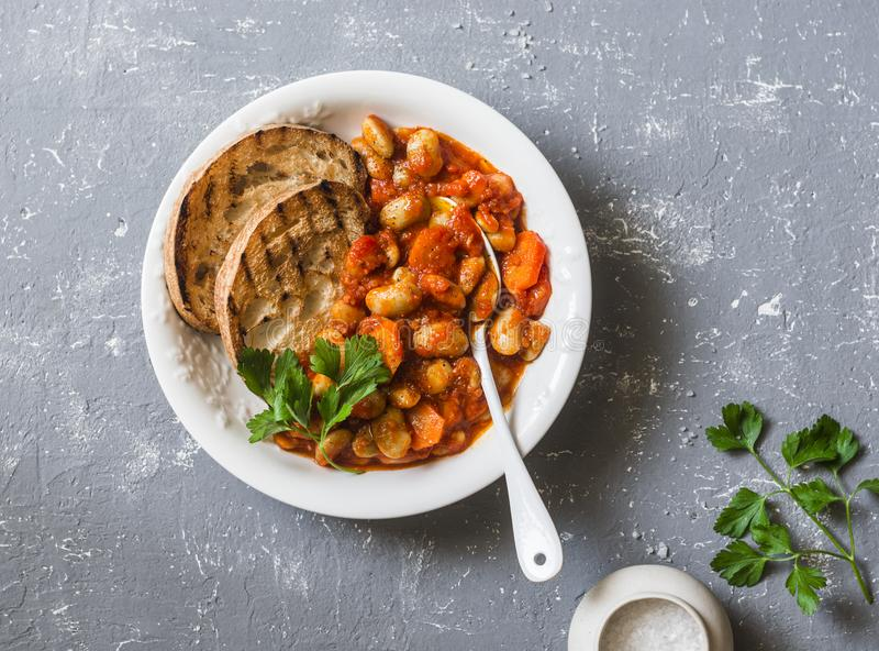 Stew beans in tomato sauce and grilled bread. Beans bruschetta. Delicious vegetarian appetizer on grey background stock image