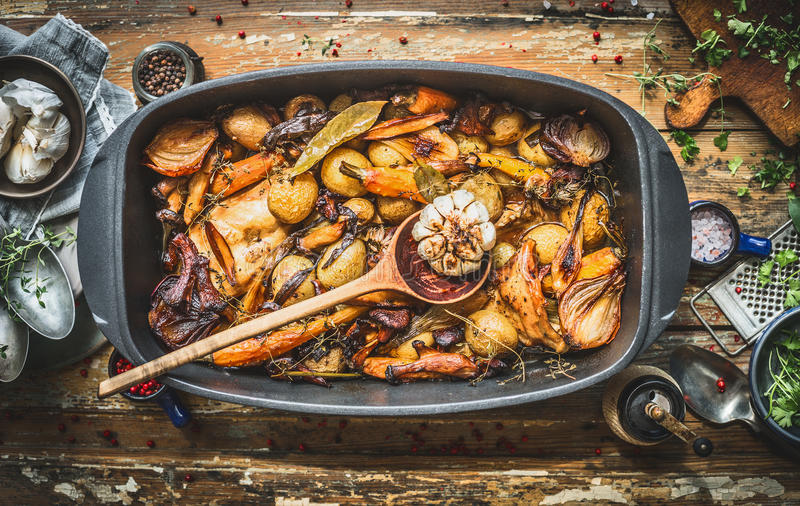 Stew with roasted vegetables, forest mushrooms and wild hunting fowl in cooking pot with wooden spoon. Rabbit ragout on rustic age stock photography