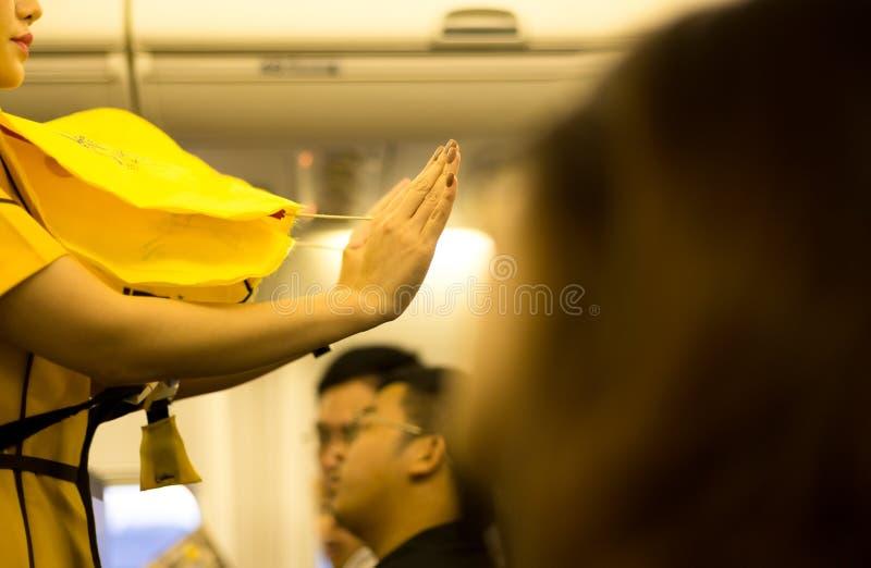 Steward (hôtesse de l'air) présent un gilet de vie à bord images libres de droits