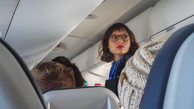 Stewardesa w szkieł spojrzeniach w kierunku plecy przeglądać nad głowami siedzący pasażery samolot obrazy royalty free